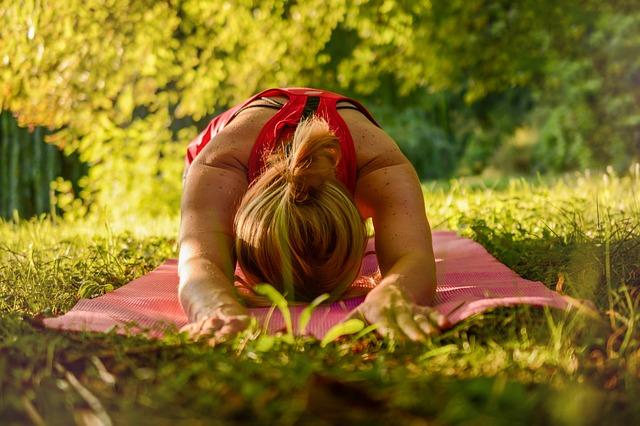 Frau in der Yoga Pose Balasana (Kind Position), auf einer roten Yogamatte in der Natur (Wiese und Bäume im Hintergrund)