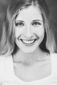 Das bin ich, die Betreiberin dieser Website. Frontales schwaz-weiß Portraitfoto. Junge Frau, dunkelblondes langes Haar, lächelnd.