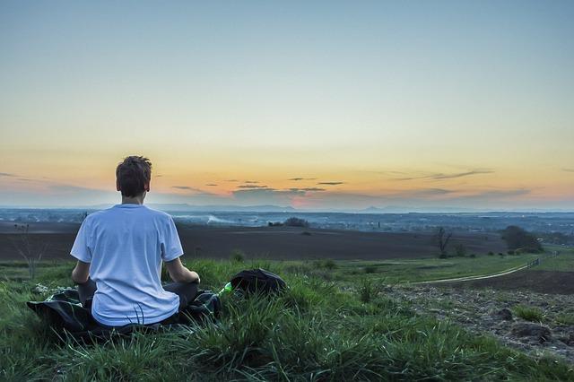 Meditierender junger Mann, sitzend auf einem Feld in der Morgendämmerung
