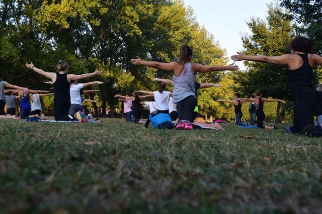 Gruppe von Menschen, die in auf einer Wiese in einem Park Yoga üben